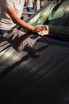 Mannhand, die um einer windschutzscheibe sich kümmert
