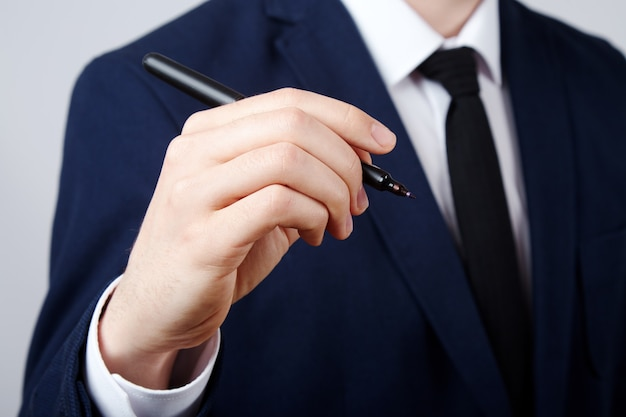 Mannhand, die weißes hemd und anzugwand, nahaufnahme, geschäftskonzept trägt, einen stift hält, schreibt.