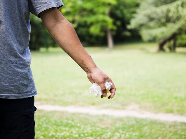 Mannhand, die zerknittertes papier am park hält