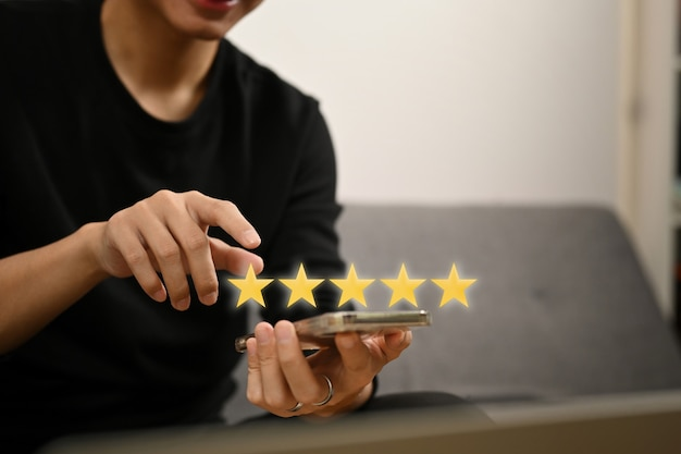 Mannhand drückt auf smartphone-bildschirm mit goldener fünf-sterne-bewertung und gibt positives feedback.