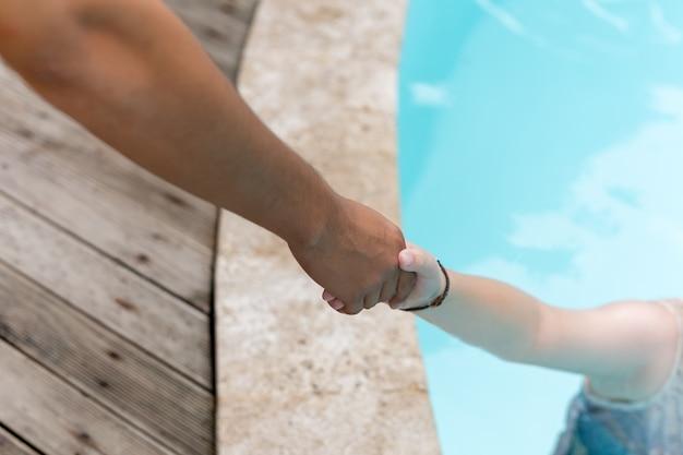 Mannhand erreichen helpnig achild in einem lokalen pool im urlaub.