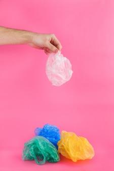 Mannhand hält weiße zerschmetterte plastiktüte über mitte und wird werfen und verschmutzen