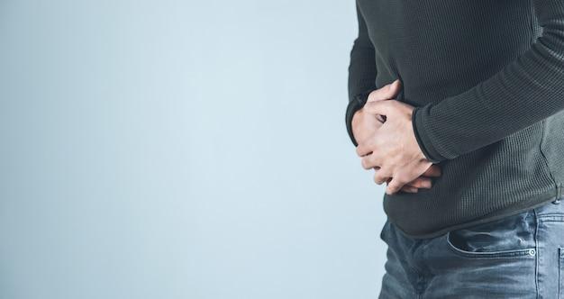 Mannhand in schmerzmagen auf grauem hintergrund