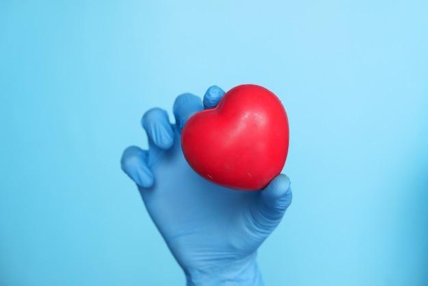 Mannhand in schutzhandschuhen, die rotes herz auf blau halten
