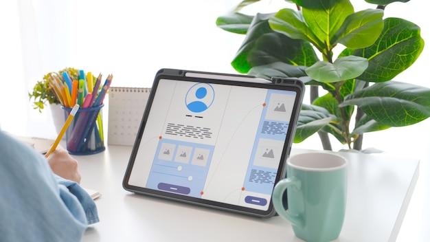 Mannhand mit bleistift und digitalem tablet mit prototyp für die entwicklung mobiler apps auf dem bildschirm, während er zu hause arbeitet