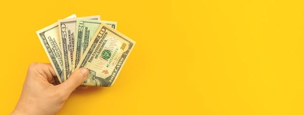 Mannhand mit dollarnoten, sparkonzept, flacher fahnenhintergrund mit kopienraumfoto