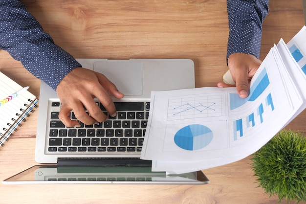 Mannhand mit stift, der balkendiagramm auf papier analysiert und laptop von oben nach unten verwendet
