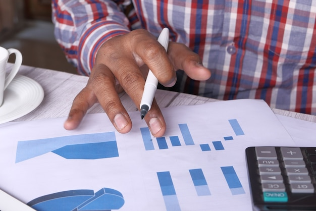 Mannhand mit stift, der balkendiagramm auf papier analysiert.