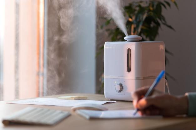 Mannhand schreibt mit stift in notizbuch nahe dem aromaöldiffusor auf dem tisch, dampf vom luftbefeuchter, selektiver fokus