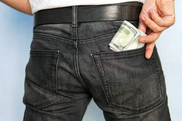 Mannhand steckt geld in die tasche. alltägliche ausgaben. ausgaben aus eigener tasche. leichtes geld.