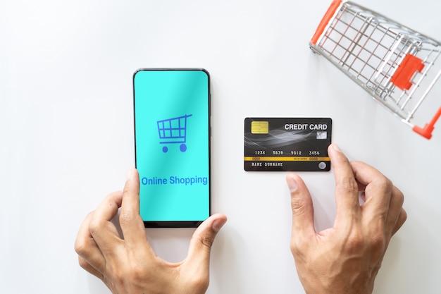 Mannhand unter verwendung des mobilen smartphone und der kreditkarte. online einkaufen