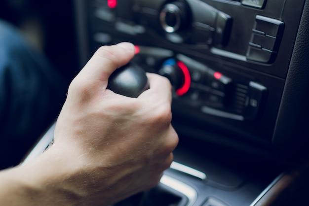 Mannhand verschiebt getriebe im autosalon. nahansicht