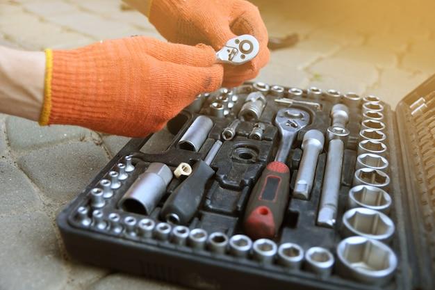 Mannhand wählt instrument im autoreparaturservice vom kasten. close up.kit von einstellbaren metallischen werkzeugen im auto-shop