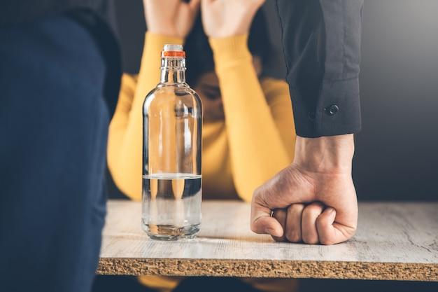 Mannhandalkohol mit trauriger frau
