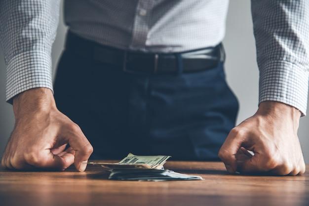 Mannhandfaust und geld auf dem schreibtisch
