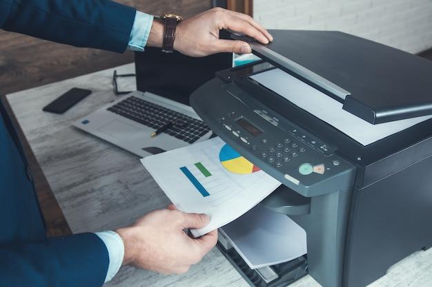 Mannhandpapier und drucker im bürohintergrund