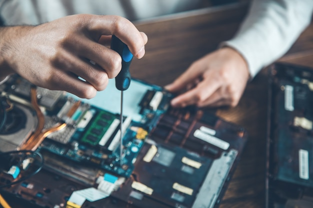 Mannhandschraubendreher mit computer auf schreibtisch