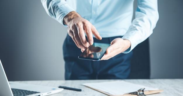 Mannhandtelefon mit dokument auf schreibtisch