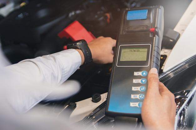 Manninspektion, die batteriekapazitäts-prüfvorrichtung voltmeter hält für service-wartung von industriellem zur motorreparatur fabriktransportautomobilautomobilbild