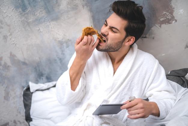 Mannkleid, das pizza isst und nach hause trinkt
