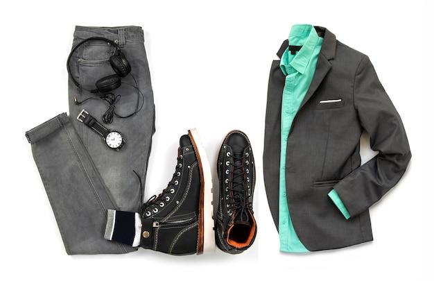 Mannkleidung stellte mit der schwarzen stiefelette, uhr, grauen jeans des kopfhörers und grauem anzug ein, die auf einem weißen hintergrund, draufsicht lokalisiert wurden