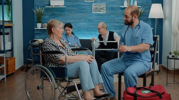 Mannkrankenschwester, der ältere frau mit behinderung im pflegeheim berät