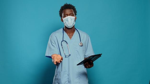 Mannkrankenschwester mit gesichtsmaske, die die coronavirus-epidemie erklärt