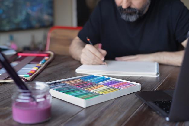 Mannkünstler, der mit bleistift und pastellstift auf papier vor laptop malt. malen lernen online-bildung