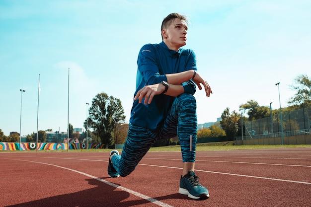 Mannläufer, der beine streckt, bereitet sich auf lauftraining auf stadionbahnen vor, die aufwärmen tun