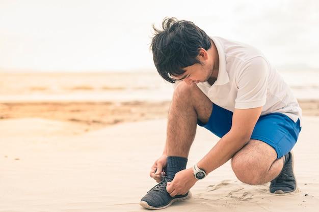 Mannläufer, der die spitze bereit bindet, auf strand zu laufen