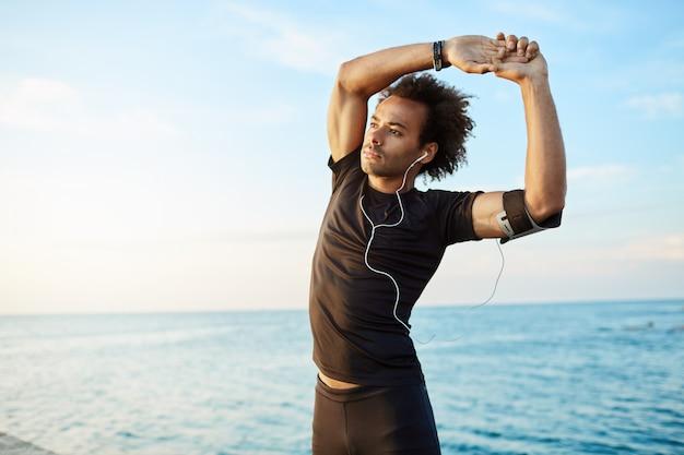 Mannläufer mit buschiger frisur, die vor aktivem training dehnt. männlicher athlet, der kopfhörer in der schwarzen sportkleidung trägt, die übungen macht.