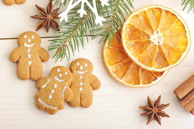 Mannlebkuchen und getrocknete orangen mit weihnachtsbaumasten