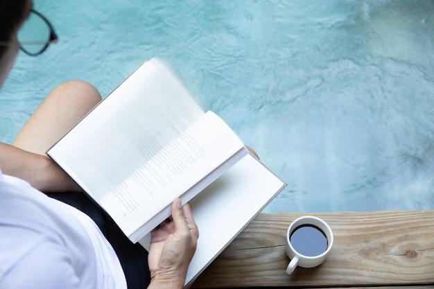 Mannlesebuch mit tasse kaffee auf bretterboden nahe bei swimmingpool.