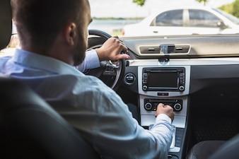Männlicher Fahrer, der Radio im Auto abstimmt