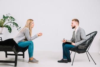 Männlicher Psychologe, der vor dem weiblichen Patienten hört auf ihr Problem sitzt