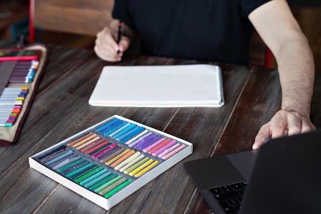 Mannmalerei mit bleistift- und pastellkreidekreide auf papier vor laptop