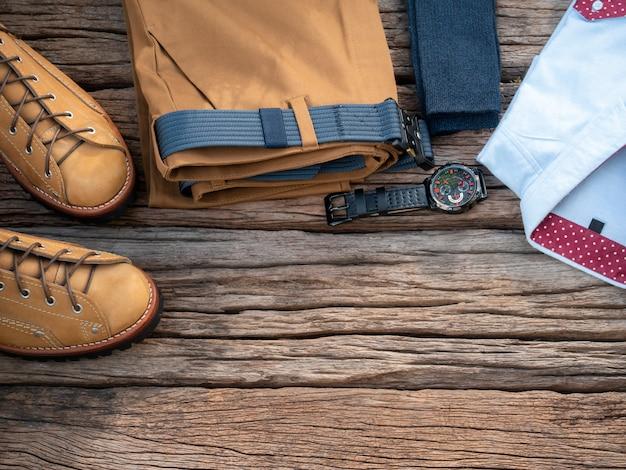 Mannmodekleidungssatz und -zubehör auf hölzernem hintergrund. ansicht von oben