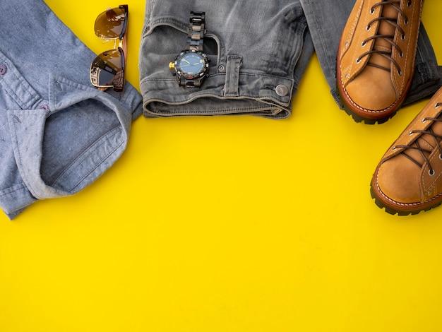 Mannmodekleidungssatz und -zubehör lokalisiert auf einem gelb. mann kleidet konzept, draufsicht
