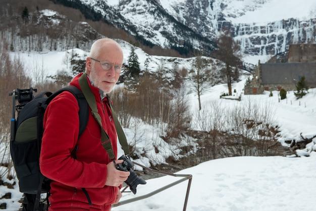 Mannphotograph mit kamera im schneebedeckten berg