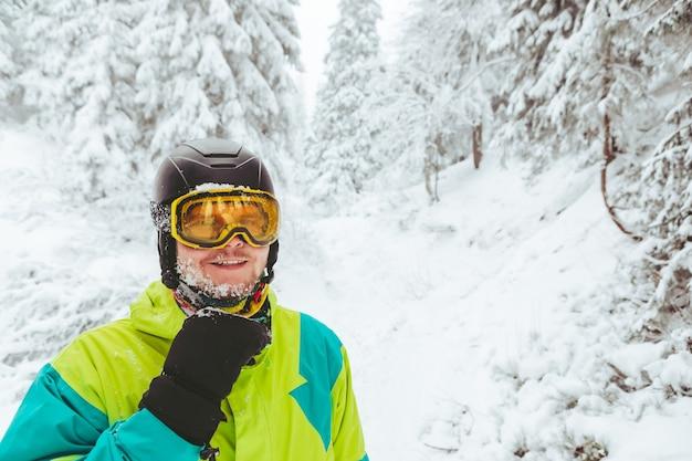 Mannporträt in der wintersaison der snowboardausrüstung