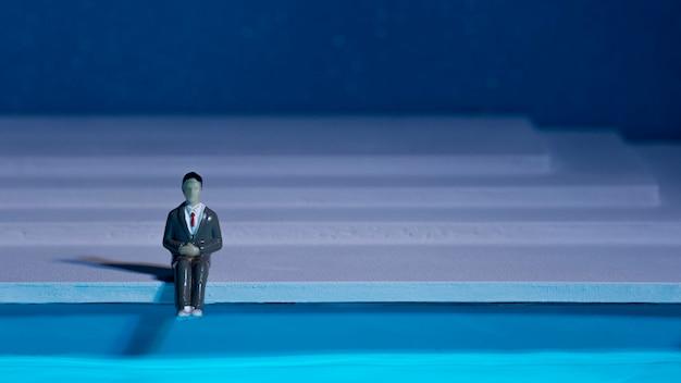 Mannpuppe, die neben schwimmbad mit kopienraum sitzt