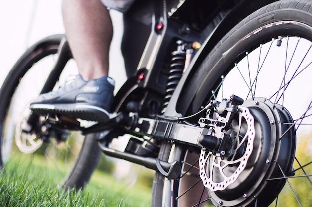 Mannradfahrer, der auf elektrischem fahrrad sitzt