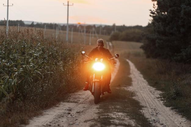 Mannreisender, der ein motorrad mit licht im feld reitet