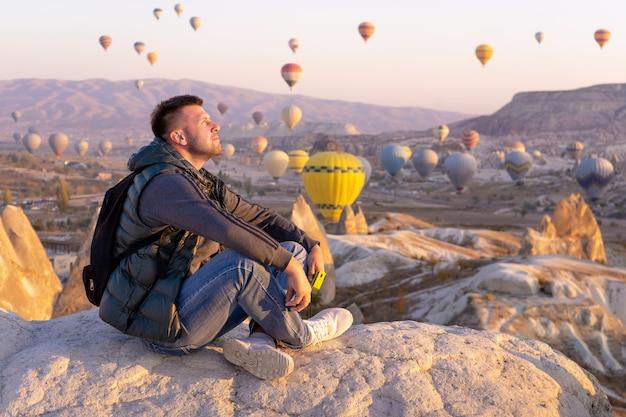 Mannreisender mit schwarzem rucksack, der die heißluftballons am hügel von göreme, kappadokien, türkei beobachtet.
