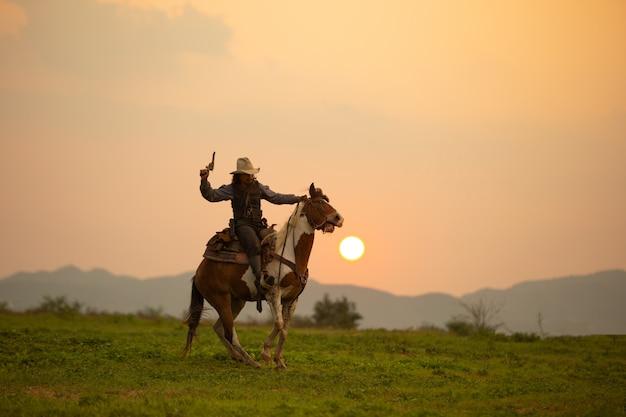 Mannreitpferd auf feld während des sonnenuntergangs
