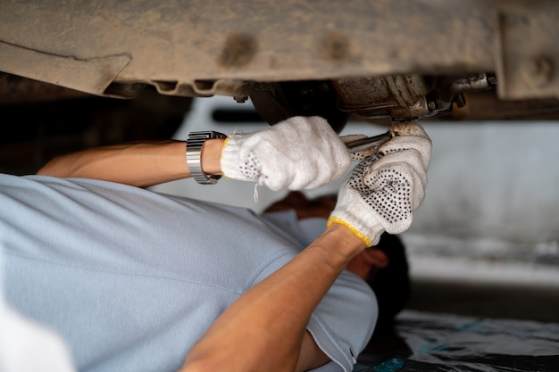 Mannreparatur- und -wartungsmotor des alten autos. konzept des sicheren fahrens und der automobilsorgfalt.