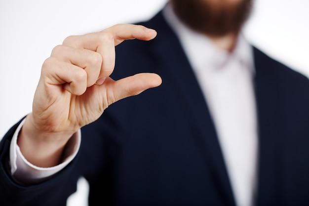 Manns hand, die anzug zeigt ein zeichen im studio