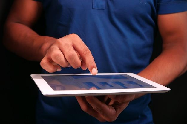 Manns hand, die auf digitalem tablett am schreibtisch arbeitet, unter verwendung des selbst erstellten diagramms.