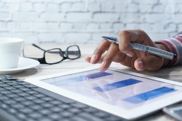 Manns hand, die auf digitalem tablett am schreibtisch arbeitet, unter verwendung des selbst erstellten diagramms