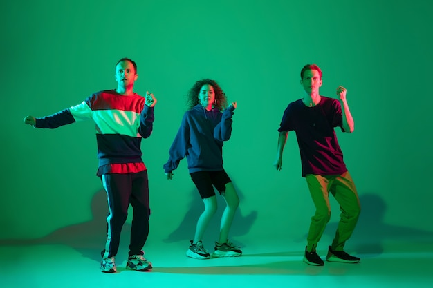Mannschaft, freunde. stilvolle männer und frauen tanzen hip-hop in hellen kleidern auf grünem hintergrund im tanzsaal im neonlicht. jugendkultur, bewegung, stil und mode, action. modisches porträt.